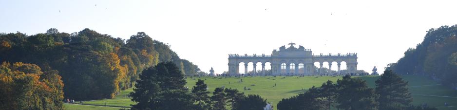Le château de Schönbrunn avec la Gloriette. Une colline légèrement grimpante est recouverte d'herbes et  bordée d'arbres. Sur le monticule se trouve la Gloriette, un bâtiment avec onzearcs. Devant le bâtiment se trouvent des personnes.