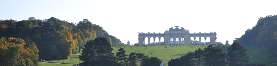 Photo: Castle ground Schönbrunn with Gloriette. Gently rising hill with grass and lined up trees. On the hilltop is a building with eleven circular arches: the Gloriette. In front of the building is a group of people.