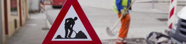 """Foto: Im Vordergrund befindet sich ein dreieckiges Verkehrszeichen. Es bedeutet """"Achtung Baustelle"""". Auf weißem Grund mit roter Umrandung ist ein Arbeiter in schwarzer Farbe abgebildet, der Erde oder Sand schaufelt. Im Hintergrund des Fotos steht ein Bauarbeiter, der eine Schaufel hält, auf einer Straße."""