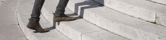 Foto: Es sind die Beine eines Mannes abgebildet, der Stufen hinaufgeht. Die Person trägt graue Jeans und braune Wildlederstiefel.
